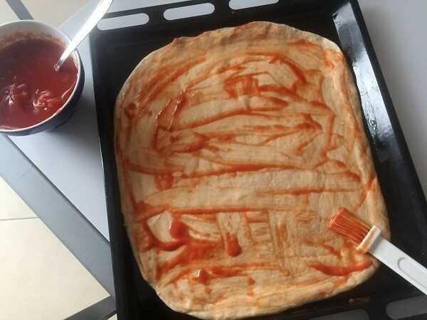 Stendere un velo di pomodoro con il pennello aiuta a rendere più saporita la pizza e ad evitare il formarsi della crosticina sulla superficie